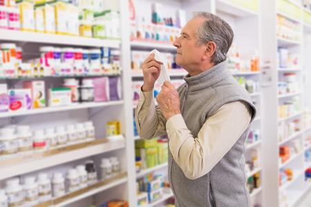 enfermos: Cliente enfermo sosteniendo un pa�uelo en la farmacia Foto de archivo
