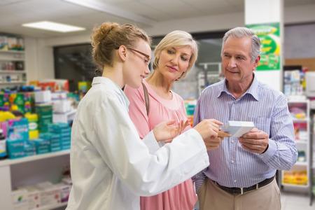 farmacia: Farmac�utico y sus clientes hablando de la medicaci�n en la farmacia