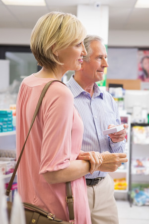 Smiling couple standing with medication in the pharmacy photo
