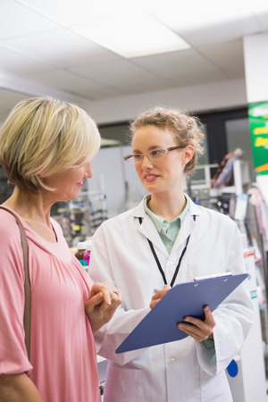 Pharmacist writing prescription with her customer in the pharmacy photo