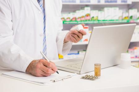 Apotheker die op klembord en het houden van medicijnen in de apotheek