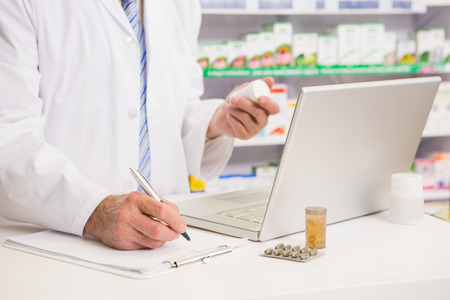 Pharmacist writing on clipboard and holding medication in the pharmacy