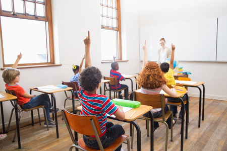Pupils raising their hands during class at the elementary school Stock Photo