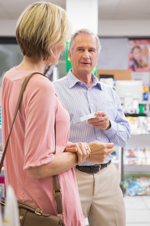 Smiling couple speaking about medication in the pharmacy photo