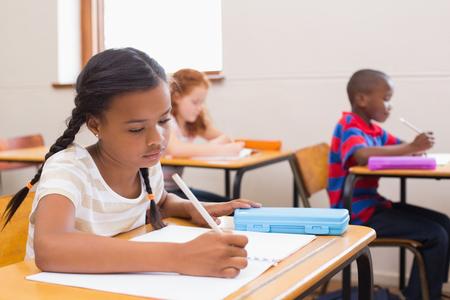 � writing: Alumnos lindos que escriben en el escritorio en el aula en la escuela primaria