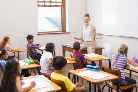 male teacher: Teacher giving a lesson in classroom at the elementary school Stock Photo