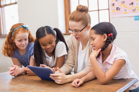 salon de clases: Profesor y alumnos que mira el ordenador tableta en la escuela primaria