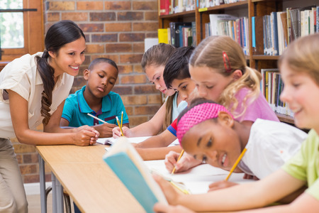 maestro: Bastante profesor de ayudar a los alumnos en la biblioteca en la escuela primaria