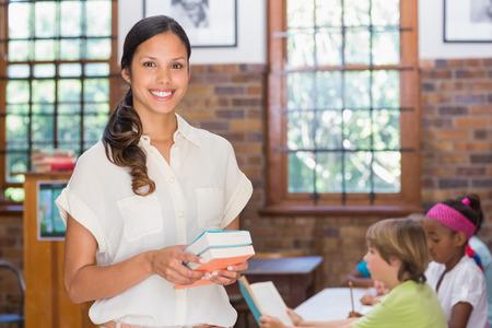 profesores: Bastante maestro sonriendo a la c�mara en la biblioteca en la escuela primaria Foto de archivo