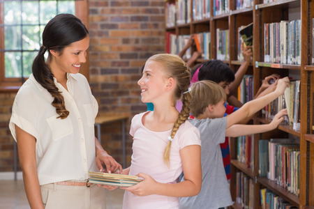 early 30s: Cute pupils and teacher looking for books in library at the elementary school Stock Photo