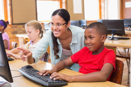 teaching adult: Cute pupils in computer class with teacher at the elementary school
