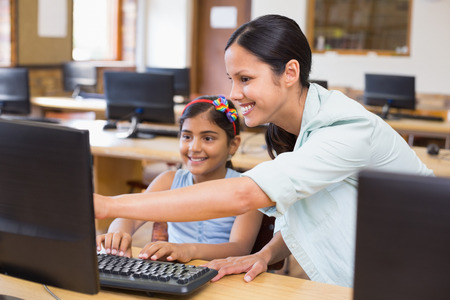 Cute pupil in computer class with teacher at the elementary school