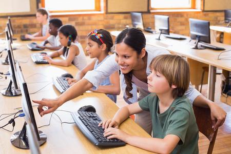 Leuke leerlingen in de computer klas met leraar aan de basisschool