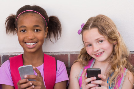 pupils: Cute pupils using mobile phone at the elementary school