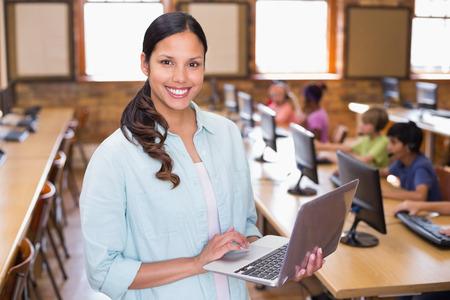 maestro: Bastante maestro usando la computadora port�til en la clase de computaci�n en la escuela primaria Foto de archivo