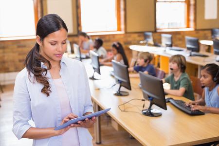educadores: Bastante maestro con tablet PC en la clase de computaci�n en la escuela primaria Foto de archivo