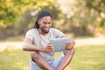 bel homme: Hippie Handsome utilisant sa tablette pc sur une journée ensoleillée
