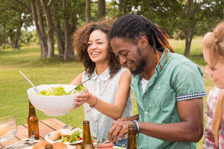 lifestyle caucasian: Happy friends in the park having lunch on a sunny day