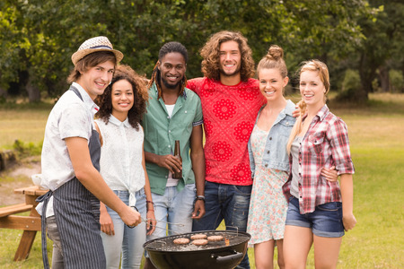 al fresco: Happy friends in the park having barbecue on a sunny day Stock Photo