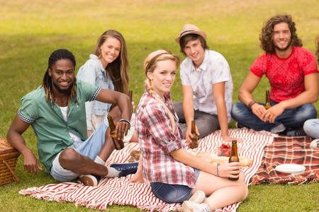 jeune fille: Amis heureux dans le parc ayant pique-nique sur une journ�e ensoleill�e