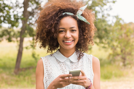 woman happy: Happy young woman using smartphone on a sunny day