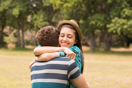 man woman hugging: Young couple hugging in the park on a sunny day