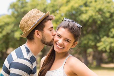 novios besandose: Linda pareja en el parque en un día soleado