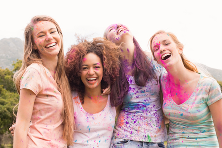 fashionable female: Happy friends throwing powder paint on a sunny day