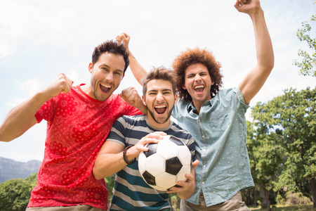 Happy friends in the park with football on a sunny day Stock Photo