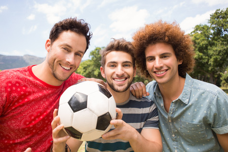 green man: Happy friends in the park with football on a sunny day Stock Photo