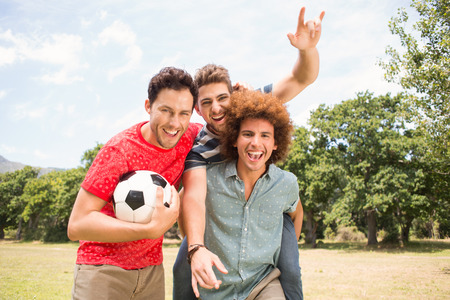 30s adult: Happy friends in the park with football  on a sunny day