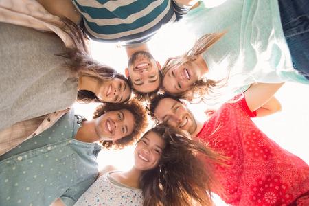 circulo de personas: Amigos felices en el parque con el f�tbol en un d�a soleado Foto de archivo