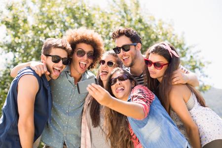 dia soleado: Amigos felices en el parque tomando Autofoto en un día soleado