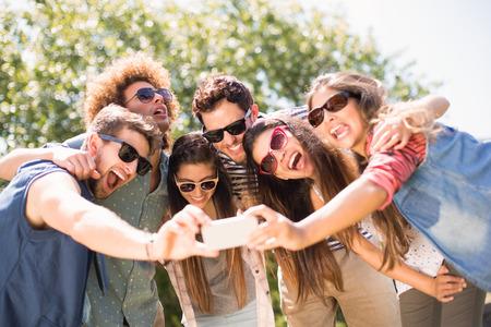 amabilidad: Amigos felices en el parque tomando Autofoto en un día soleado