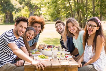 to lunch: Amigos felices en el parque de almorzar en un d�a soleado
