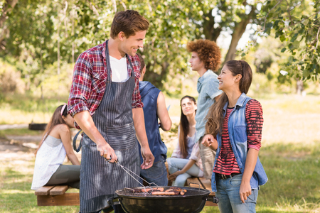 picnic food: Happy friends in the park having barbecue on a sunny day Stock Photo