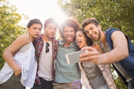 AMIGOS: Amigos felices en el parque tomando Autofoto en un d�a soleado