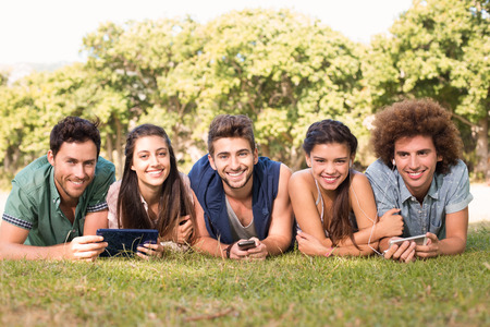 girl friend: Happy friends in the park using their phones on a sunny day
