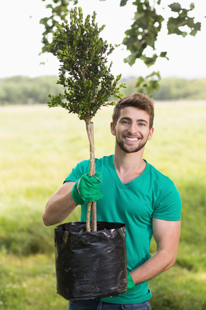 sembrando un arbol: Hombre joven feliz jardiner�a para la comunidad en un d�a soleado