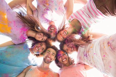 circulo de personas: Amigos felices cubiertos de pintura en polvo en un día soleado Foto de archivo