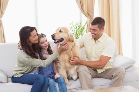 Familia cariñosa perro acariciando mientras está sentado en el sofá en casa