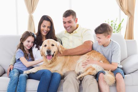 Familia feliz de cuatro acariciando perro perdiguero de oro en el salón