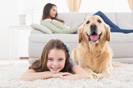Portret van gelukkig meisje met een hond die op tapijt, terwijl de moeder ontspannen thuis