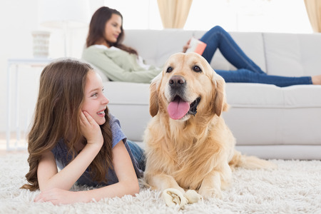 female child: Happy girl looking at dog while lying on rug at home
