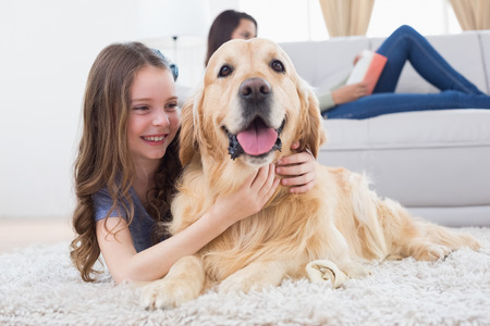 hug: Happy girl embracing Golden Retriever while lying on rug at home