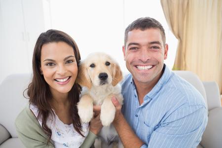 beau jeune homme: Portrait d'un couple heureux holding chiot à la maison