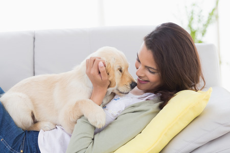 golden retriever puppy: Beautiful woman playing with puppy while lying on sofa at home Stock Photo