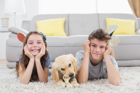 Portrait of happy siblings with puppy lying on rug at home Stock Photo