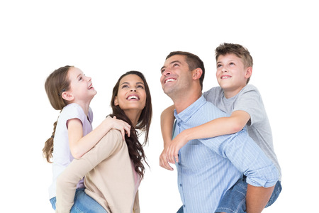 Happy parents giving piggyback ride to children while looking up over white background photo