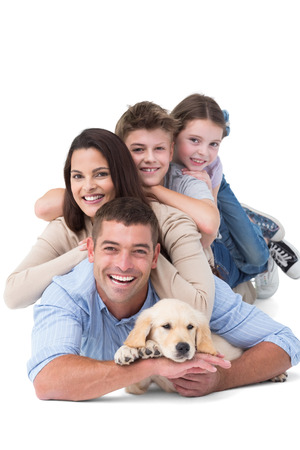 Portrait of happy family lying on top of each other with dog over white background
